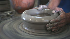 Close up of hands working clay on potter's wheel stock video footage