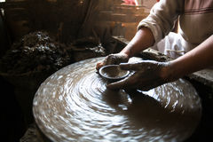 Close-up of hands working clay on potter's wheel. Work in the studio potter Stock Photos