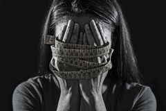 Hands wrapped in tailor measure tape covering face of young depressed and worried girl suffering anorexia or bulimia nutrition dis. Close up hands wrapped in stock images