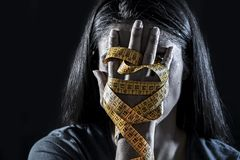 Hands wrapped in tailor measure tape covering face of young depressed and worried girl suffering anorexia or bulimia nutrition dis Royalty Free Stock Image