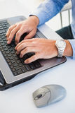 Close up of hands with wrist watch typing on laptop Royalty Free Stock Images