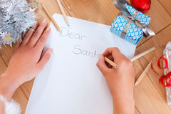 Christmas list of wishes. Close up of hands writing a christmas list of wishes for santa stock photo