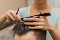 Close up of hands of young barber making haircut to attractive man in barbershop.  Stock Photo
