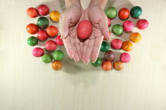 Close up hands of young christian holding colorful easter eggs on marble top with copyspace background Stock Photography