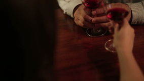 Close up of hands of young loving couple clinking glasses of red wine. Romantic dinner in the restaurant stock footage