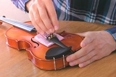 Close-up hands of young man in plaid shirt is repairing a violin sitting at the table. Tightens the bolts into place. stock photo