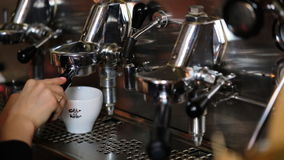 Close up of hands of young waitress preparing coffee in professional coffee machine in a cafeteria. stock video