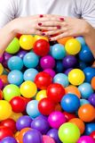 Close-up of hands of a young woman with colorful plastic balls. stock image