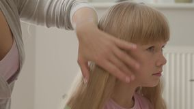 Close-up hands of young woman combing her cute blond daughter. Concept of motherhood, childhood. Leisure indoors. Happy. Family stock video footage