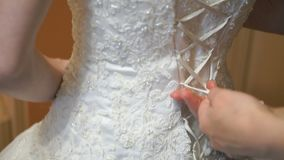 Bride getting dressed up for the wedding. Close-up of hands of young woman friend tying white ribbons of a corset wedding bridesmaid dresses stock video footage