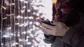 Close-up hands young woman using smartphone in the falling snow at Christmas night standing near lights wall, Royalty Free Stock Photos