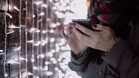 Close-up hands young woman using smartphone in the falling snow at Christmas night standing near lights wall, stock video footage