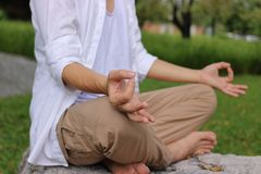 Close up hands of young yogi man doing yoga meditation while sitting in lotus position on the rock in the park. royalty free stock images
