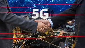 Close up of handshake on abstract city and 5g background.Teamwork concept. Double exposure. Filtered image. royalty free stock image