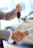 Close up of handshake in auto show or salon Stock Image