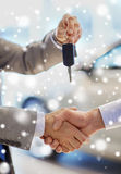 Close up of handshake in auto show or salon Royalty Free Stock Photography