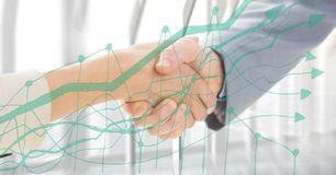 Close up of handshake behind green graph against window Stock Photo