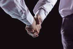 Concept of a reliable partnership: a close-up of handshake of business partners on a black background. Stock Photos