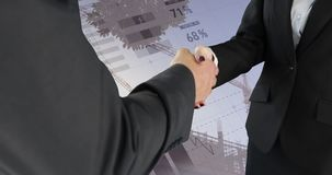 Handshake between business people 4k. Close up of a handshake between a businessman and a businesswoman. Behind them is a digital animation of graphs and stock footage