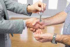 Close up of a handshake and a key delivery Royalty Free Stock Image