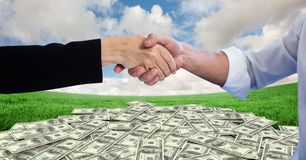 Close-up of handshake with money in background stock photography