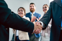 Close-up of the handshake of two business men after an important agreement. Close-up on handshake of two business men in applauses of three employees, after an stock photos
