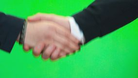 Handshake of two people. Close-up. Close-up of handshake of two unknown fellow man and woman against green wall background stock footage