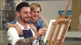 Close up of a handsome artist drawing at his studio while his wife hugging him. Close up of a handsome happy bearded male artist working on his painting at his vector illustration