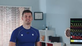 Close-up of handsome athlete walking on treadmill and smiling. During stress test in modern sports lab stock footage
