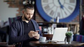 Close up of handsome bearded man dressed in black t-shirt and blue jacket is sitting in cafe using modern laptop and. Close up of handsome bearded man dressed in stock footage