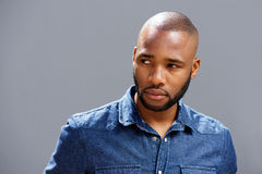 Close up handsome black guy looking away against gray wall Stock Photos