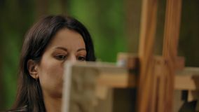 Close-up of a handsome girl brunette artist painting picture on canvas. A detailed face expression of focused emotions on a favorite hobby of drawing. A young stock video footage