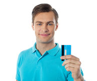 Close-up of handsome guy holding a credit card. Handsome guy holding credit card and showing to camera Stock Images