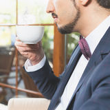 Close-up handsome male drinking a cup of espresso coffee Stock Photos