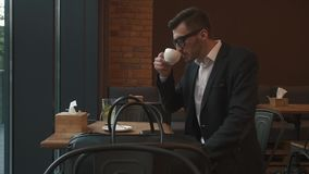 Close-up handsome male model businessman drinking a cup of espresso coffee. Hot beverage. Lunch time. Close-up handsome male model businessman drinking a cup of stock video footage