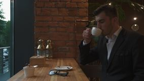 Close-up handsome male model businessman drinking a cup of espresso coffee. Hot beverage. Lunch time. Coffee break at. The office. Man dressed in elegant stock video