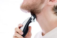 Close up handsome male shaving his own beard with a machine isolated. Close up handsome male shaving his own beard with machine isolated Royalty Free Stock Photos