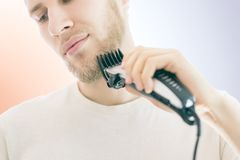 Close up handsome male shaving his own beard with a machine isolated. Close up handsome male shaving his own beard with machine isolated Stock Image