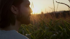 Close up of handsome man with beard with nature landscape in sunset/sunrise.