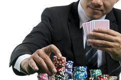 Close up at handsome man in black suit is putting piles of chips Royalty Free Stock Photography