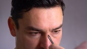 Close up handsome man in front of a mirror cares for his face. pulls out excess hair from his. Cream, expression. Beautician plucking a men eyebrows with stock footage