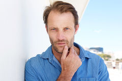 Close up handsome man leaning on wall and staring. Close up portrait of handsome man leaning on wall and staring Royalty Free Stock Image