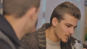 Close-up - handsome man with mustache talking with friend in bar. Close-up, camera focuses on face of man. The man looks on his friend and talks with him. Young stock footage