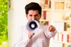 Close up of a handsome man screaming with a megaphone in a blurred background Stock Photos