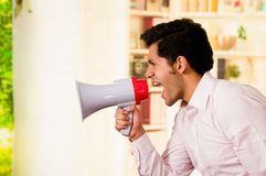 Close up of a handsome man screaming with a megaphone in a blurred background Stock Images