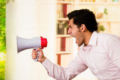 Close up of a handsome man screaming with a megaphone in a blurred background Stock Photo