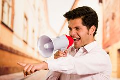 Close up of a handsome man screaming with a megaphone, pointing his hand to someone, in a blurred city background Royalty Free Stock Photography