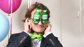 Close up of handsome man wearing beer sunglasses in party photo booth stock footage