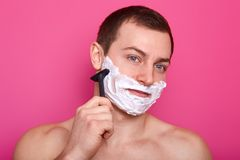 Close up of handsome shirtless man stands isolated over pink background. Guy with naked shoulders holds razor. Boy shaves and does royalty free stock image