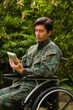 Close up of a handsome soldier sitting on wheel chair using his tablet with both hands, and wearing military uniform in. A nature background Stock Photos